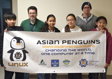 members of asian penguins student group, standing with a white banner held in front of them